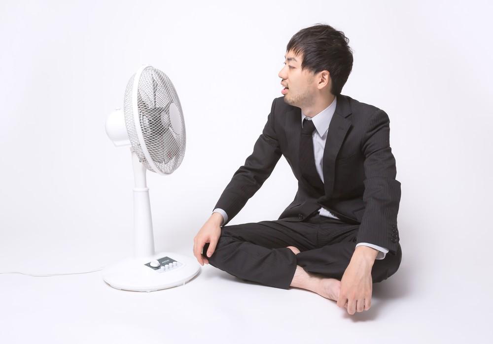 扇風機に当たる男